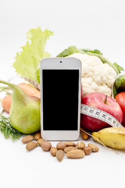 白い背景で野菜と空白の表示電話 無料写真