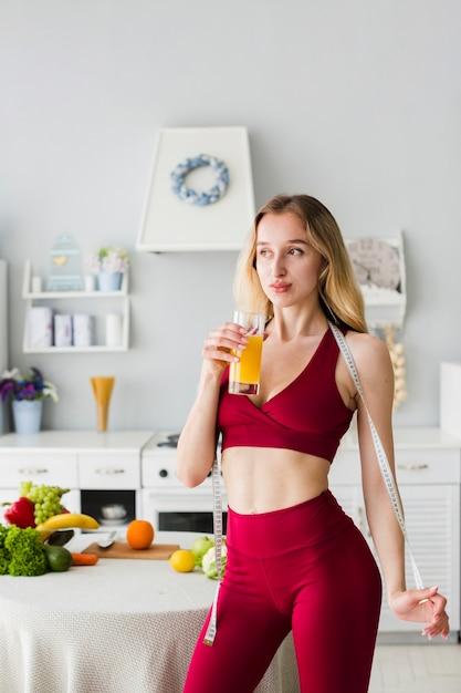健康的なジュースとキッチンでスポーティな女性 無料写真