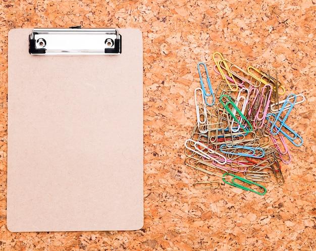 クリップボードとコルクの背景に色とりどりのペーパークリップ 無料写真