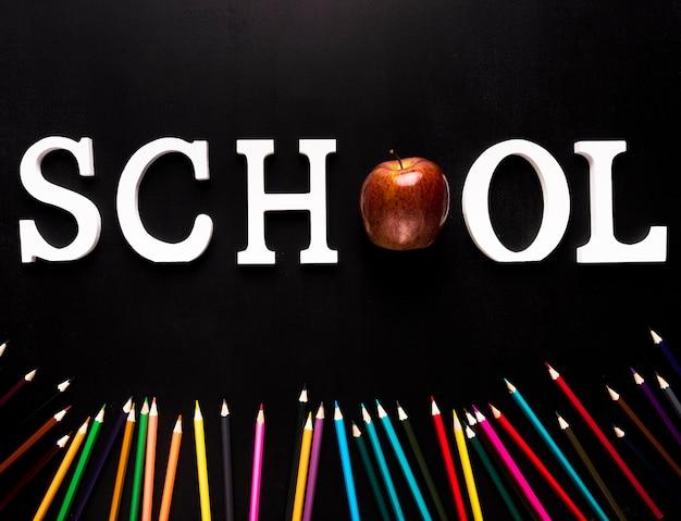 学校の単語と黒の背景に散らばった色鉛筆 無料写真