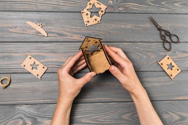 木製の机の上の段ボールから家を作る人間の手 無料写真