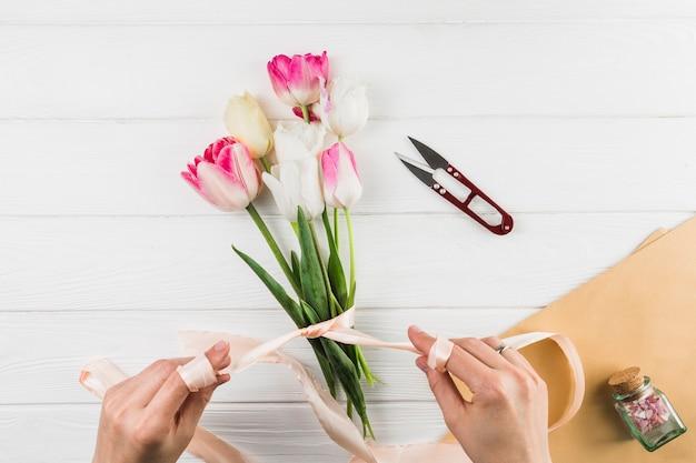 白い机の上のリボンとカッターを使用しながらチューリップの花の花束を作る女性の手のクローズアップ 無料写真