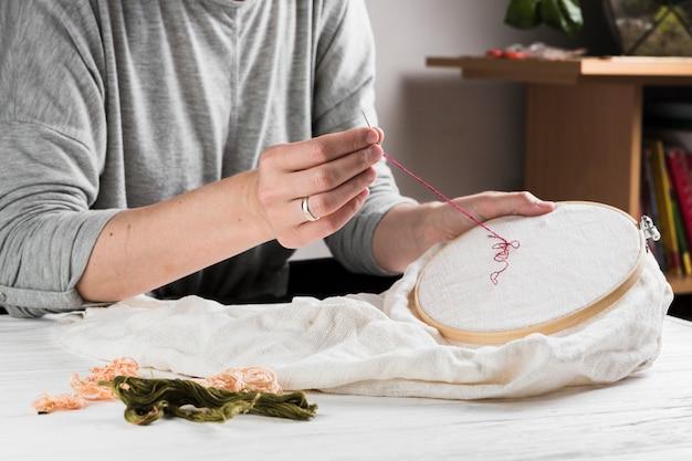 フープに赤い糸を持つ女性縫製刺繍パターン 無料写真