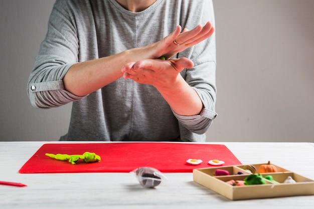 女性の手が工芸品を作るための粘土を混練 無料写真