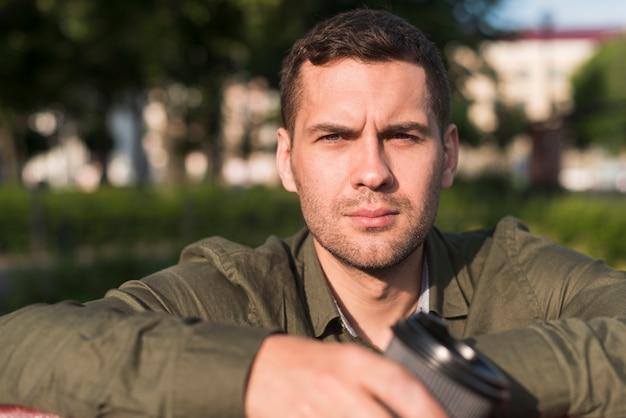 公園でカメラを見て深刻な若い男の肖像 無料写真