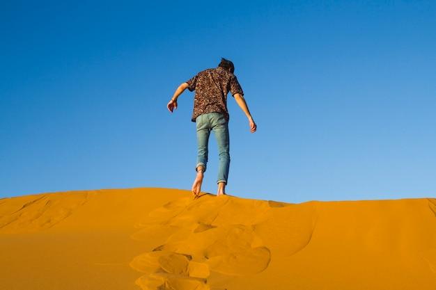 砂漠の砂丘の上を歩く男 無料写真