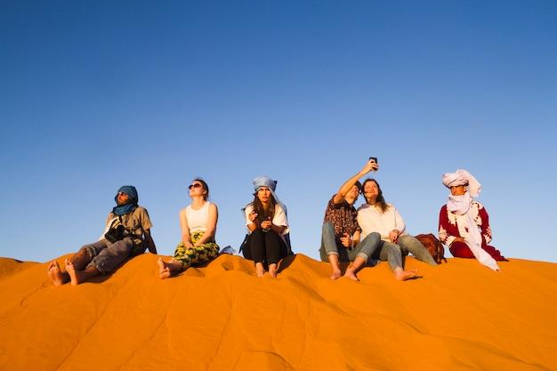 砂丘の上に座っている人々のグループ 無料写真