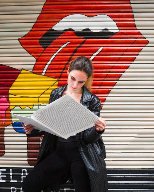 Среднего выстрела стоя женщина читает бумагу Бесплатные Фотографии
