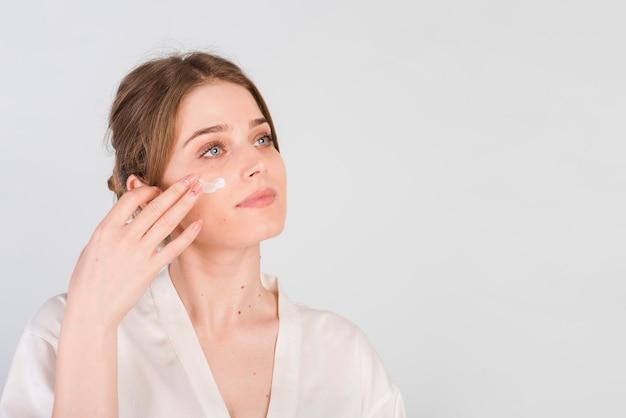 自分自身を化粧品を適用する女の子 無料写真