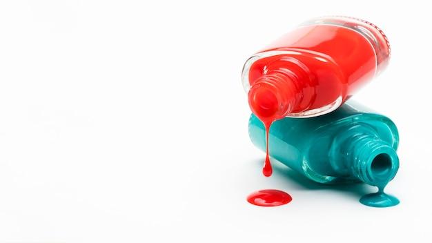 Красный и зеленый лак для ногтей пролился из бутылки с белой копией пространства фоне Бесплатные Фотографии