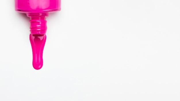 明るいピンクのマニキュア液ボトルと少し白い背景にこぼれた 無料写真