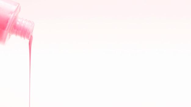 白い背景の上に注ぐピンクのマニキュア 無料写真