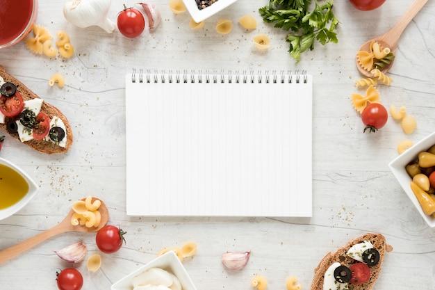 生のパスタと白いテーブルの上のイタリアの食材に囲まれた空白のメモ帳 無料写真