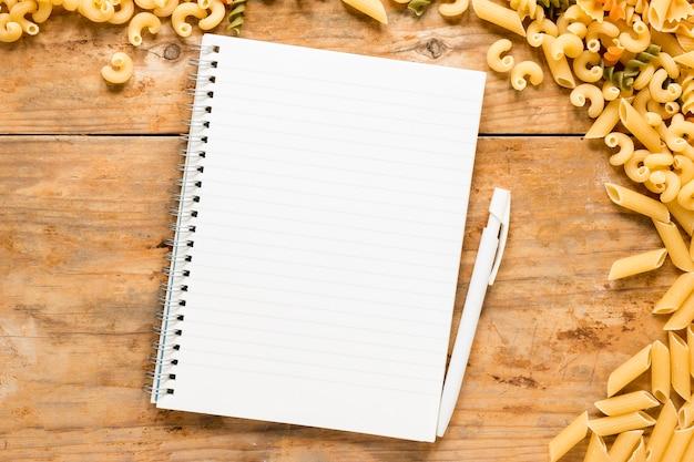 生パスタのテーブルの上の空白のスパイラルメモ帳 無料写真