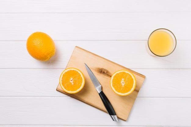 Половинки апельсина на разделочную доску со стаканом сока на белом столе Бесплатные Фотографии