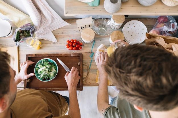 キッチンカウンターで朝食を作る友人の高角度のビュー 無料写真