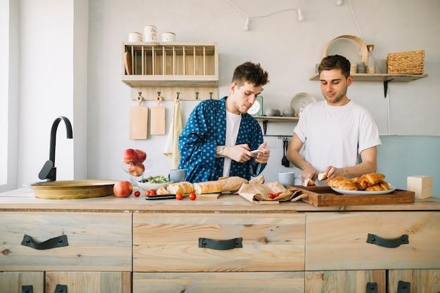 Красивый мужчина с помощью мобильного телефона, стоя возле своего друга резки яблоко на деревянной стойке Бесплатные Фотографии