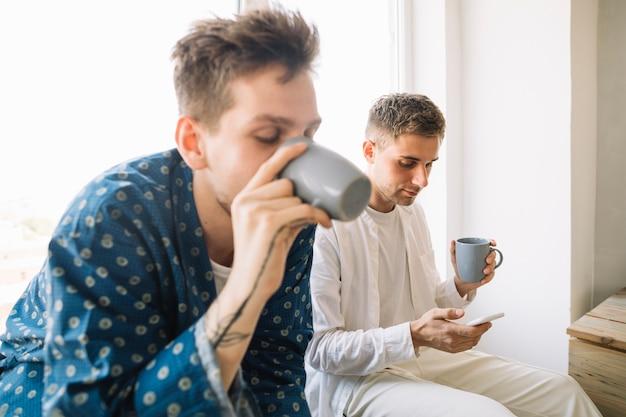 Мужчина пьет кофе, сидя возле своего друга с помощью смартфона Бесплатные Фотографии