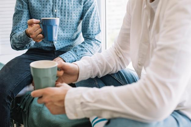 Крупный план руки двух друзей, держа чашку кофе Бесплатные Фотографии