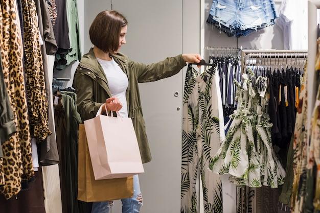 若い女性が別の衣装を選ぶ 無料写真