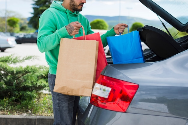 買い物袋を車内に保管する人 無料写真