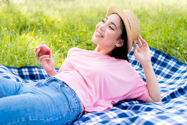 アジアの女性の布の上に横たわるアップル 無料写真