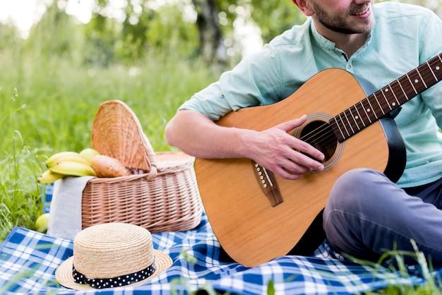 格子縞の上に座って、ギターを弾く男 無料写真