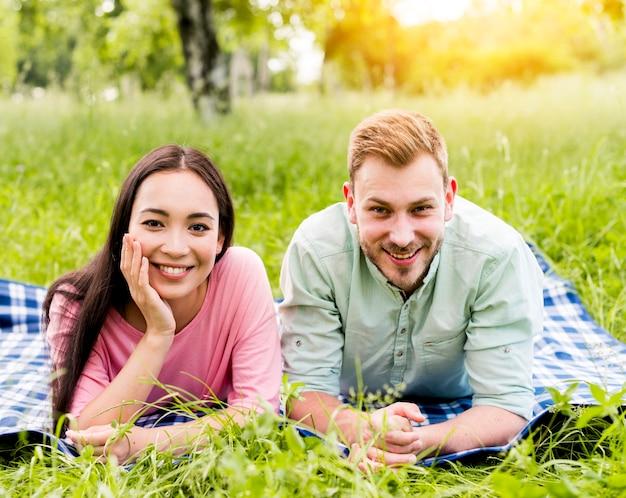 Счастливая пара многорасовых позирует на пикник Бесплатные Фотографии