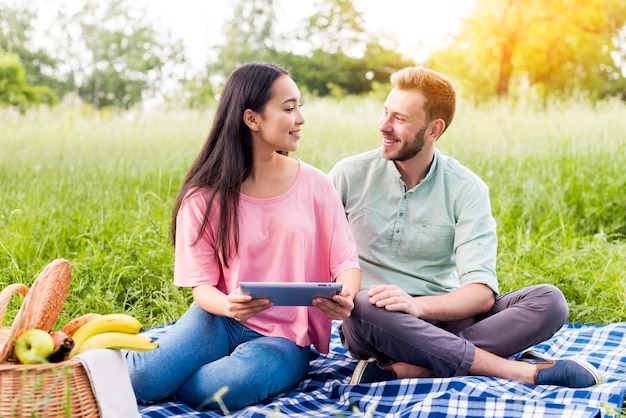 公園でタブレットをカップルします。 無料写真