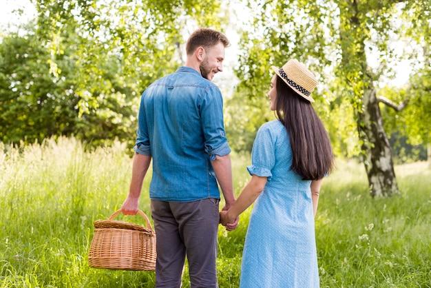 公園で手を繋いでいる恋に幸せな笑みを浮かべてカップル 無料写真