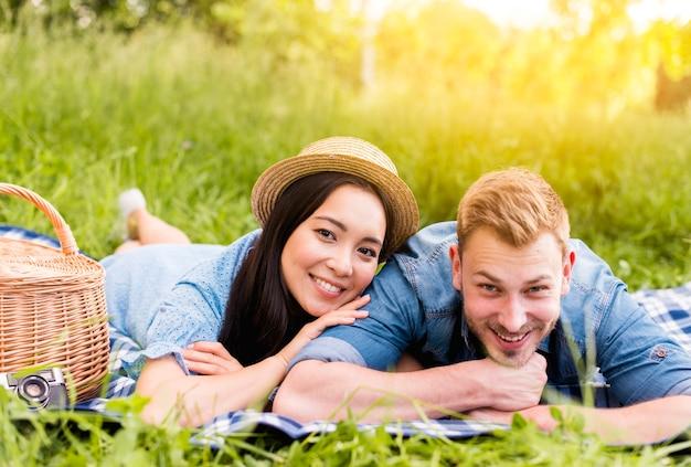 カメラを見て、ピクニックに笑顔若い美しいカップル 無料写真