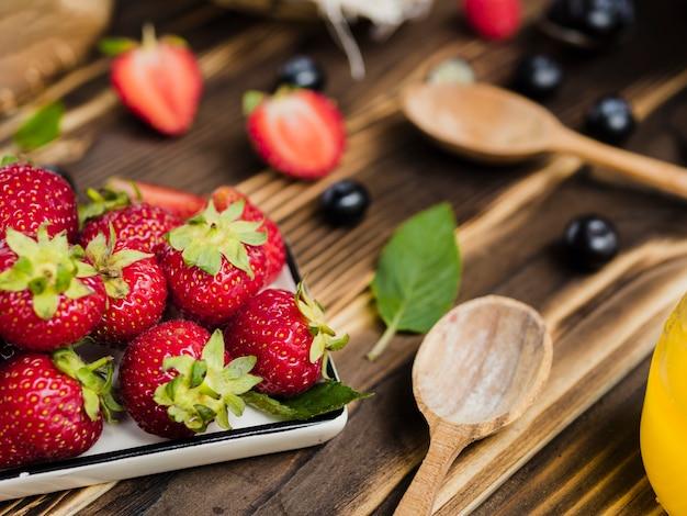 甘い新鮮なイチゴと木製の背景にスプーン 無料写真