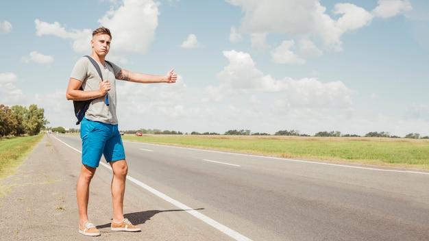 男は道路でヒッチハイク 無料写真