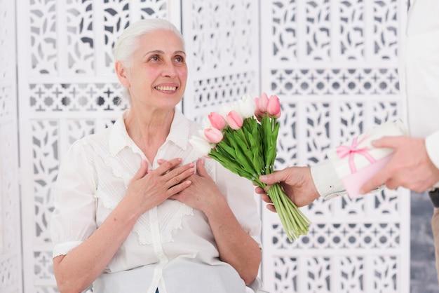 彼女の誕生日に彼の幸せな妻にチューリップの花とギフトボックスの花束を与える男 無料写真