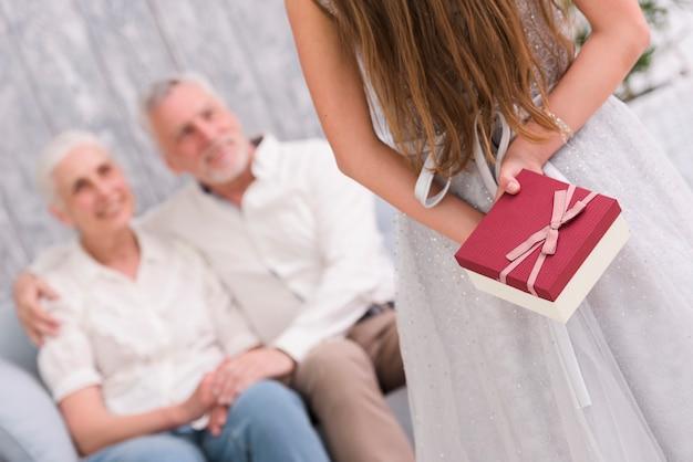Маленькая девочка прячет подарок за спиной перед бабушкой и дедушкой, сидя на диване Бесплатные Фотографии