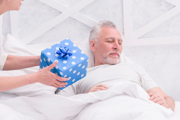 女性がベッドで寝ている彼女の夫への贈り物 無料写真