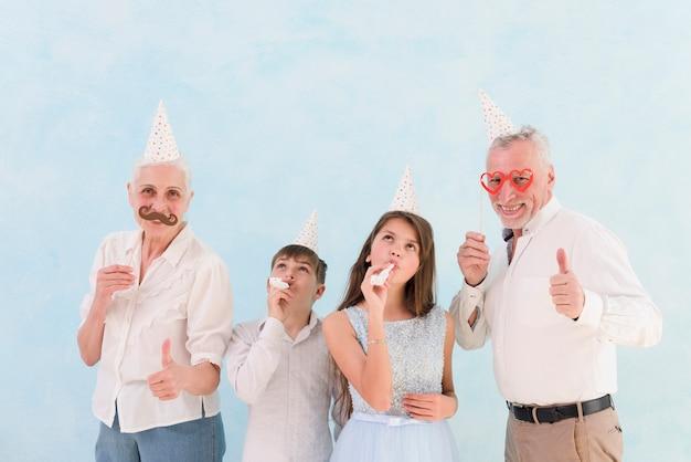 パーティーの角を吹いている彼らの孫と紙の小道具を示す幸せな祖父母 無料写真