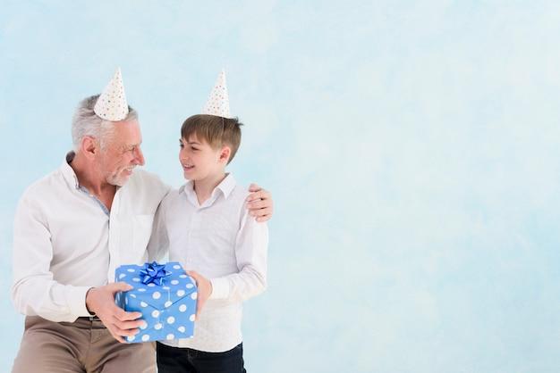 彼の誕生日に彼の祖父に青いギフトボックスを与える少年 無料写真