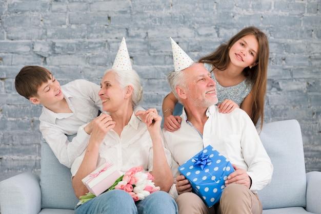 誕生日パーティーを楽しんでいる彼らの孫を見て幸せな祖父母 無料写真
