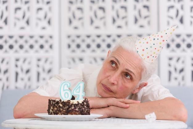 Рассматриваемая старшая женщина положила голову на стол возле торта ко дню рождения Бесплатные Фотографии