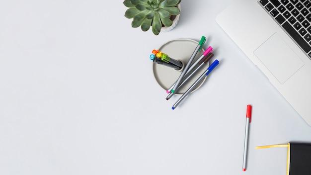 Офисный рабочий стол с ноутбуком и другими элементами Бесплатные Фотографии