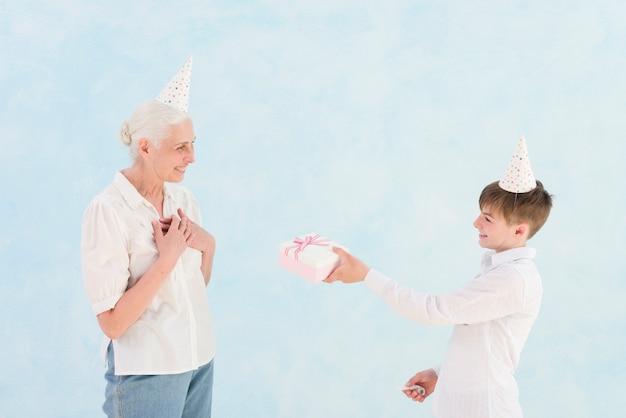 青い背景の前で彼の祖母に誕生日プレゼントを与える微笑む少年 無料写真
