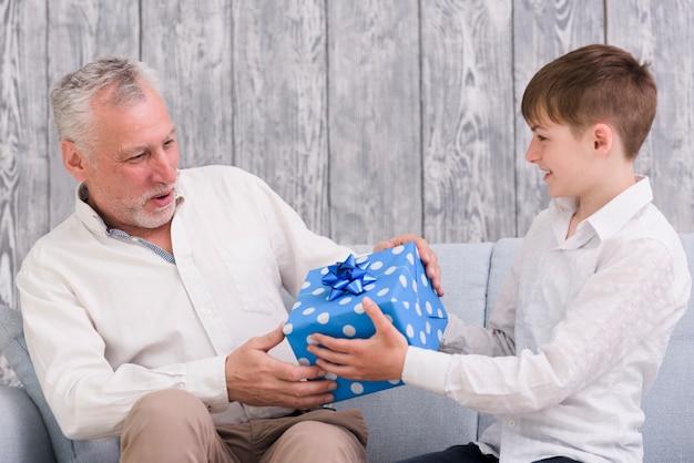 彼の祖父に青いラップ誕生日ギフトボックスを与える少年 無料写真