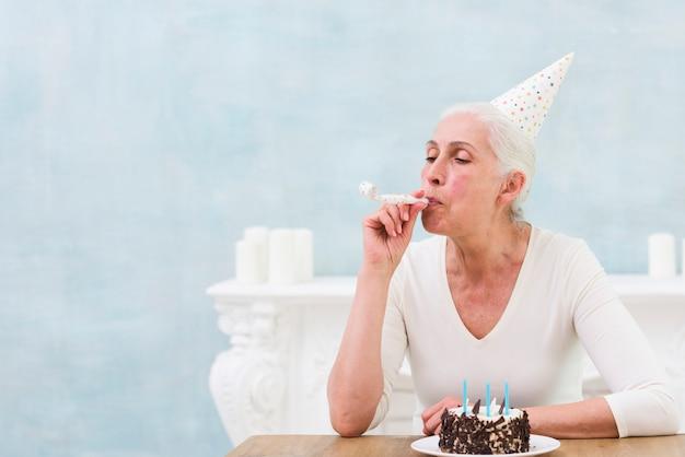 Старший день рождения женщины дует вечеринка рога в передней сладкий торт Бесплатные Фотографии
