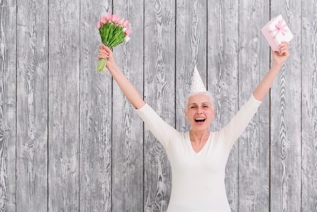Портрет улыбающегося день рождения женщины, держащей букет цветов с подарочной коробке перед деревянными фоне Бесплатные Фотографии
