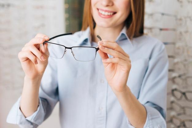 Счастливая женщина ищет новые очки у оптометриста Бесплатные Фотографии