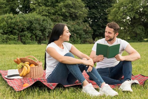 ピクニック毛布でポーズをとるカップル 無料写真