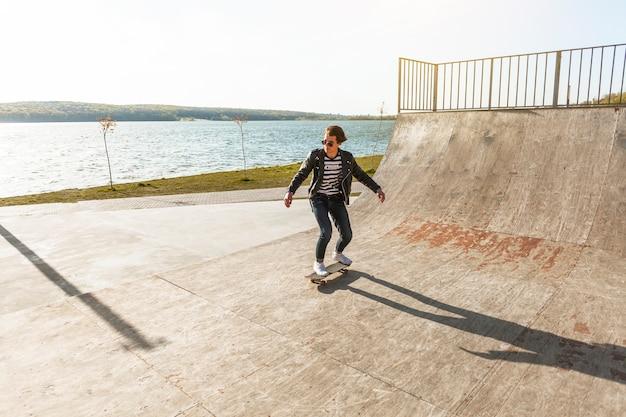 スケート公園で彼のスケートボードを持つ若者 無料写真