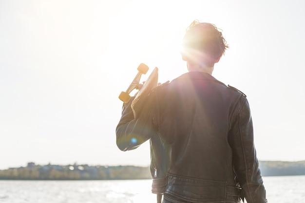 海のそばのスケートボードを持つ若い男 無料写真