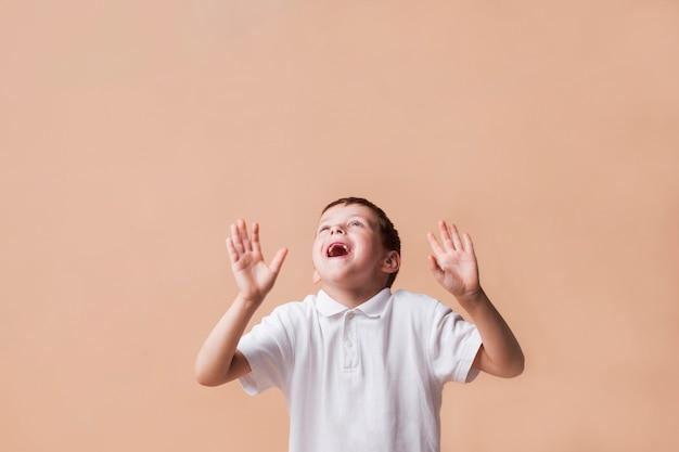 ベージュ色の背景に身振りで示す手で見上げる笑っている少年 無料写真